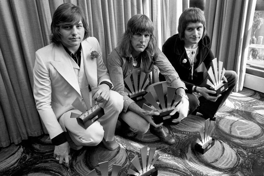 """This is a Sept. 30, 1972, file photo of  the members of the rock band Emerson, Lake and Palmer,Greg Lake, left Keith Emerson, centre, and Carl Palmer after an award ceremony in London . Greg Lake, the prog-rock pioneer who co-founded King Crimson and Emerson, Lake and Palmer, has died. He was 69. Lake died Wednesday Dec, 7, 2016, after """"a long and stubborn battle with cancer,"""" according to his manager. Photo: PA File Via AP    / PA"""