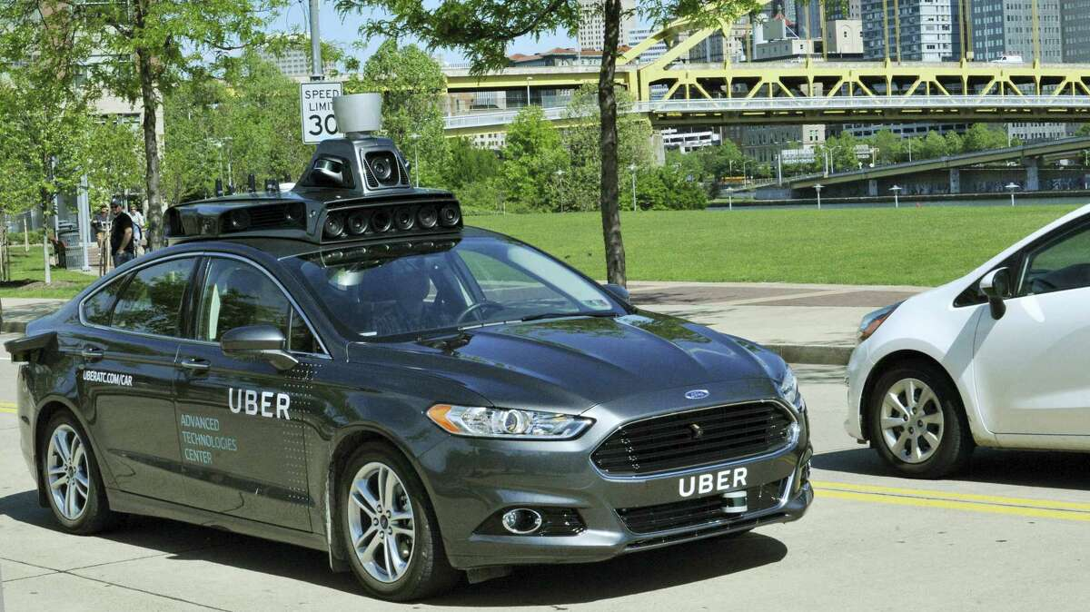 A Ford Fusion hybrid outfitted with radars, laser scanners and high-resolution cameras drives along the streets of Pittsburgh. Uber said Thursday, Aug. 18, 2016, that passengers in Pittsburgh will be able to summon rides in self-driving cars with the touch of a smartphone button in the next several weeks. The high-tech ride-hailing company said that an unspecified number of autonomous Ford Fusions with human backup drivers will pick up passengers just like normal Uber vehicles. Riders will be able to opt in if they want a self-driving car, and rides will be free to those willing to do it, spokesman Matt Kallman said.
