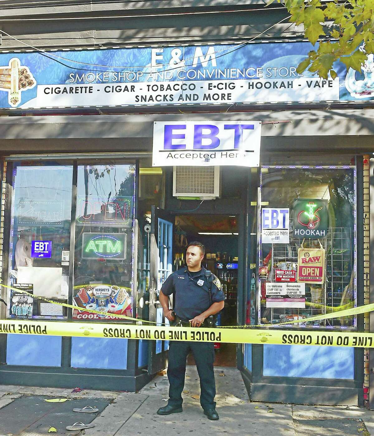 A New Haven police officer stands in front of the E&M Smoke Shop and Convenience Store at 545 Ferry St. in New Haven, where Muhanad Jawad, 21, was shot and killed Tuesday afternoon.