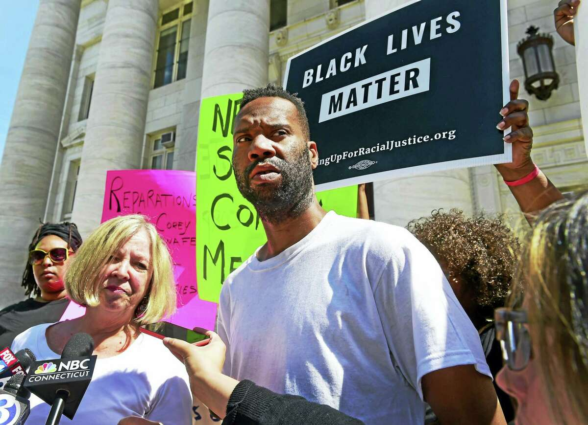 Lawyer Patricia Kane of New Haven, second from left, with her client Corey Menafee, a former employee at Yale's Calhoun College who was arraigned for breaking a Calhoun College window pane depicting black slaves picking cotton, right, talk with the press as they leave New Haven Superior Court on Elm Street in New Haven.
