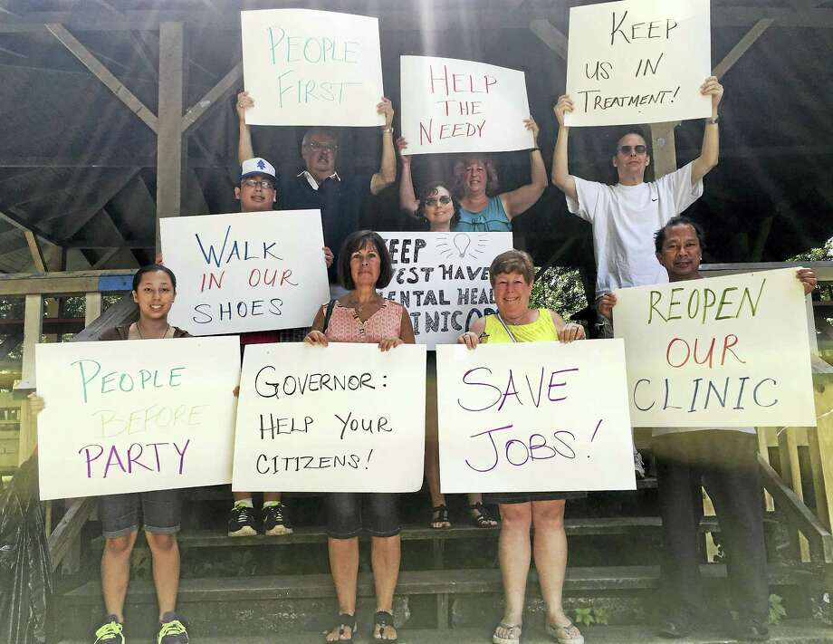 Back row: George Chambrelli, Lisa Corvera, Jonathan Bober. Middle: Remy Corvera, Sharon Rose Cappella. Front: Leanna Corvera, Susan Gallagher, Lori Bober Weinstein and Gerry Corvera protested the closing of the West Haven Mental Health Clinic on Saturday. Photo: Sam Norton — New Haven Register