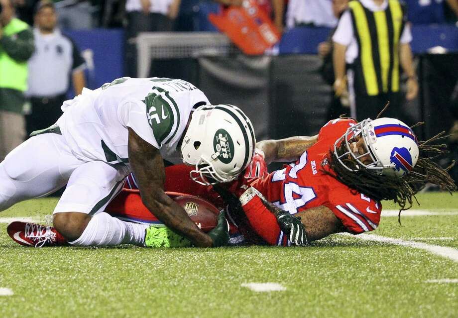 New York Jets wide receiver Brandon Marshall (15) is injured while being tackled by Buffalo Bills cornerback Stephon Gilmore (24) during the first half Thursday. Photo: Bill Wippert — The Associated Press   / FR170745 AP