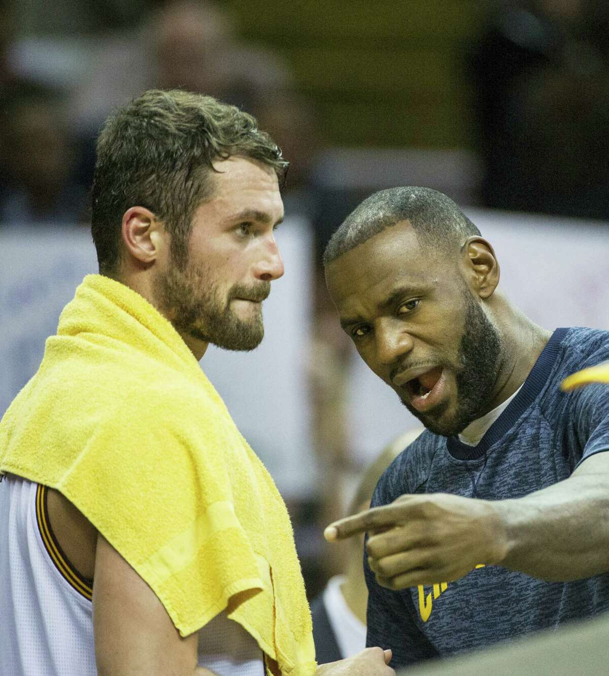 Cleveland Cavaliers' Kevin Love (0) listens to LeBron James during a time out during the first half of an NBA preseason basketball game in Cleveland on Oct. 13, 2016.