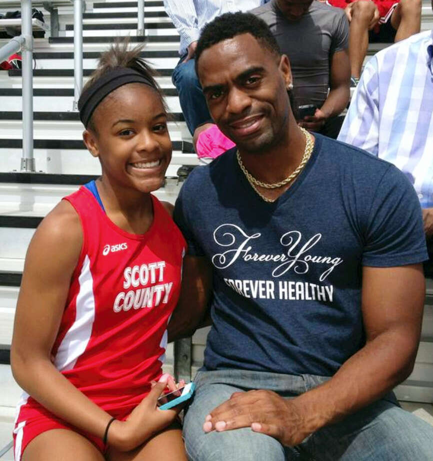In this photo, Trinity Gay, a seventh-grader racing for her Scott County High School team, poses for a photo with her father Tyson Gay. Photo: Mark Maloney — Lexington Herald-Leader Via AP   / Lexington Herald-Leader