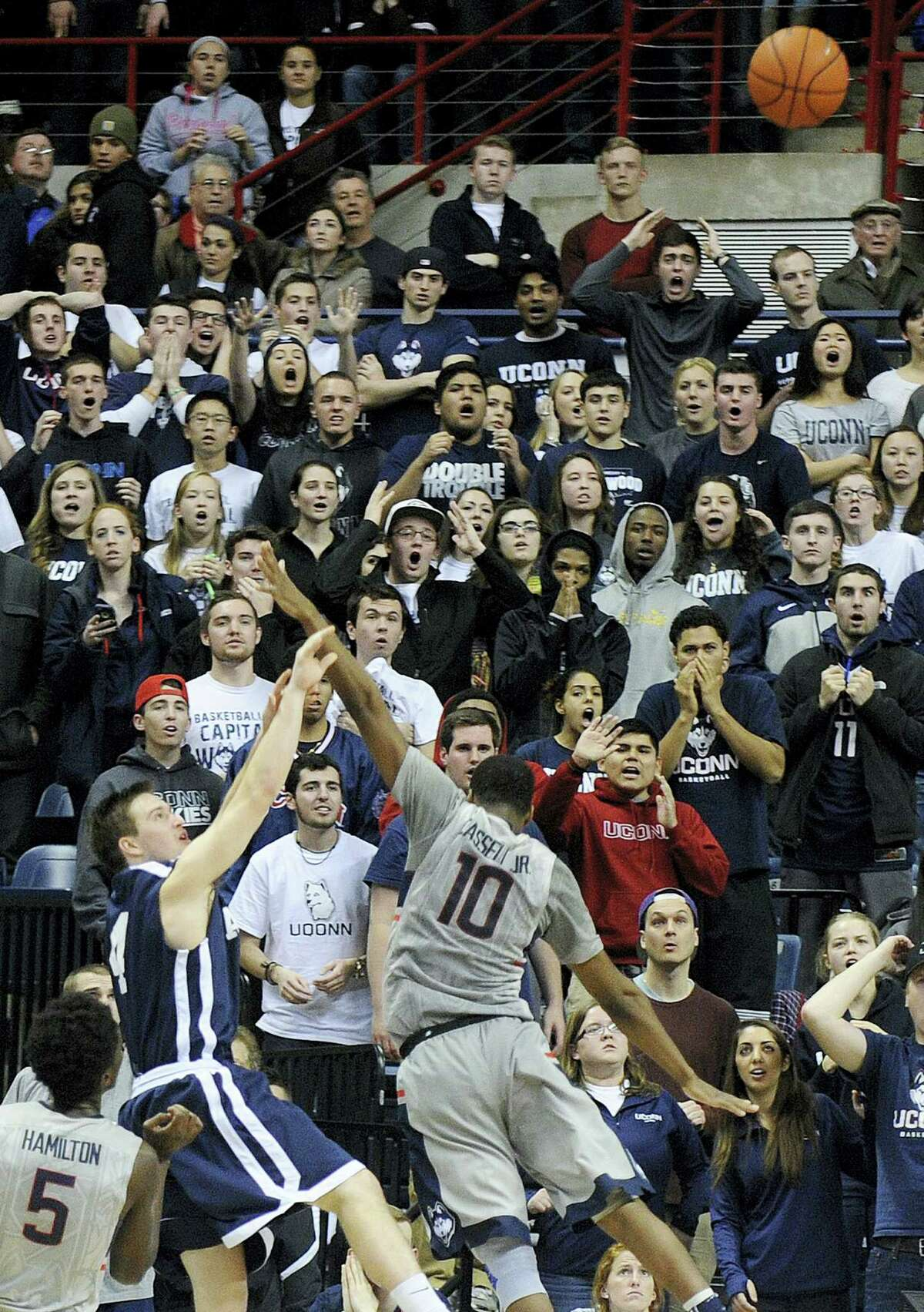 Yale's Jack Montague (4) shoots a game winning three-point shot while being guarded by Connecticut's Sam Cassell Jr. (10) during the second half of Yale's 45-44 upset victory in an NCAA college basketball game in Storrs, Conn., on Sunday, Dec. 5, 2014.