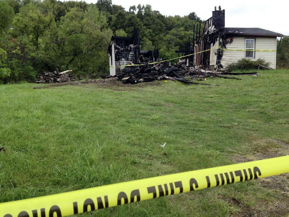 Police tape cordons off the remains of a house. Wednesday, Sept. 14, 2016, in rural Richland County, near Mansfield, Ohio, where authorities say a woman's body was found nearby. Police say a suspect in the abduction of a woman in neighboring Ashland on Tuesday confessed to killing a woman in the house in June, which was then destroyed in a fire. Photo: AP Photo/Ann Sanner    / ap