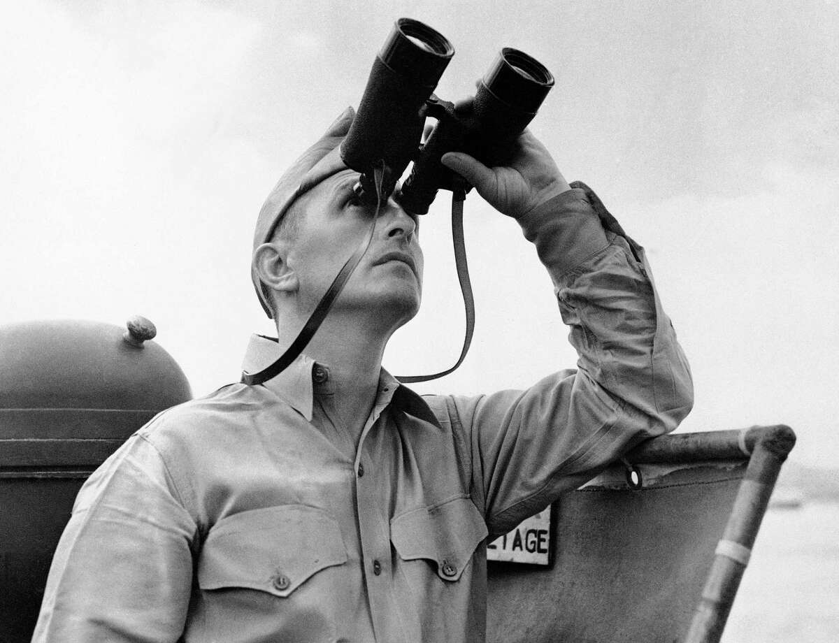 This October 1942 file photo shows Eugene Burns, Associated Press war correspondent with the Pacific Fleet, on the deck of a Navy vessel with binoculars raised as he covered operations of a task force in the South Pacific. On Dec. 7, 1941, as Japanese bombs rained down on Pearl Harbor, Burns, Associated Press chief of bureau in Honolulu, was unable to get out the urgent news of the historic attack that would draw the U.S. into World War II. The military had already taken control of all communication lines, so Burns was left without a line to the outside world.