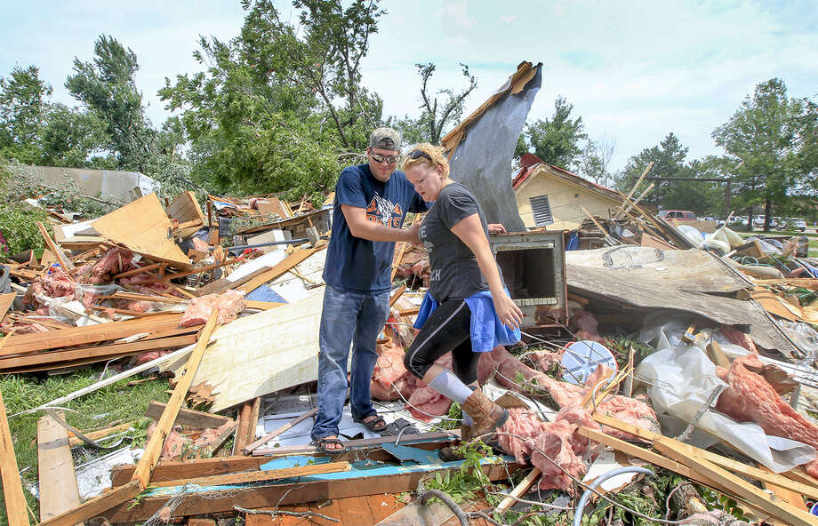 A tornado warning sounded in Arkansas Thursday night, forcing two presidents and a prime minister to take shelter in a school while a tornado actually hit Kansas at the same time. In this photo, Toby Hennessy and Samantha Levieux check out the damage to his home in Eureka, Kan. The National Weather Service says two tornadoes ripped through southeast Kansas late Thursday, causing widespread damage in Eureka, a town of roughly 2,600 residents east of Wichita. Photo: Fernando Salazar/The Wichita Eagle Via AP    / The Wichita Eagle