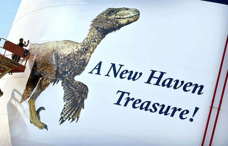 Shawn Martel of Merritt Graphics applies sections of a mural of the dinosaur, Deinonychus, on a 90,000-barrel heating oil tank at Magellan Midstream Partners, Inc., at New Haven Harbor earlier this week. Photo: Photo By Arnold Gold — New Haven Register