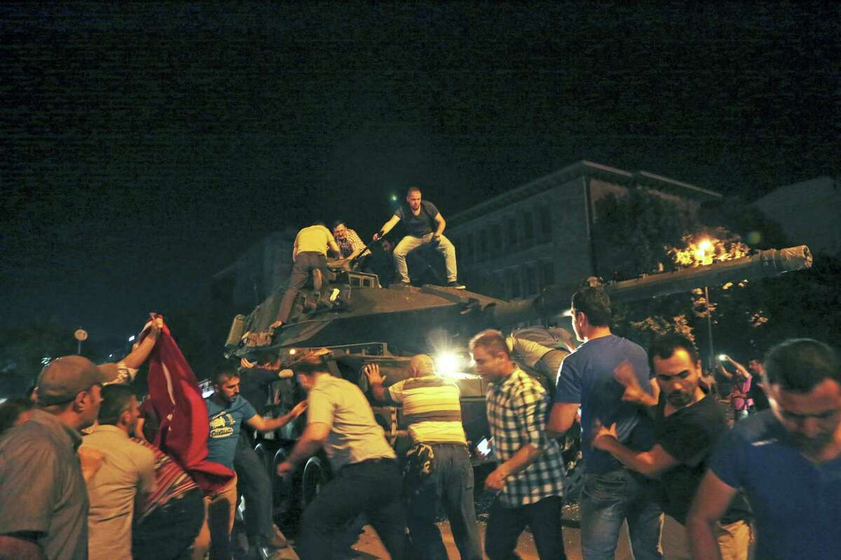 Turkish people attempt to stop a tank moving into position in Ankara, Turkey, late Friday, July 15, 2016. Members of Turkey's armed forces said they had taken control of the country, but Turkish officials said the coup attempt had been repelled early Saturday morning in a night of violence, according to state-run media.