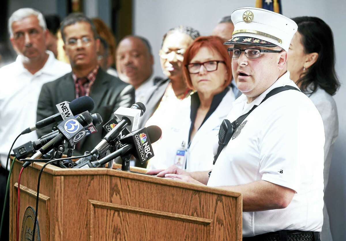 New Haven Fire Department Assistant Chief Matt Marcarelli, right, speaks at a press conference at the New Haven Police Department in June.