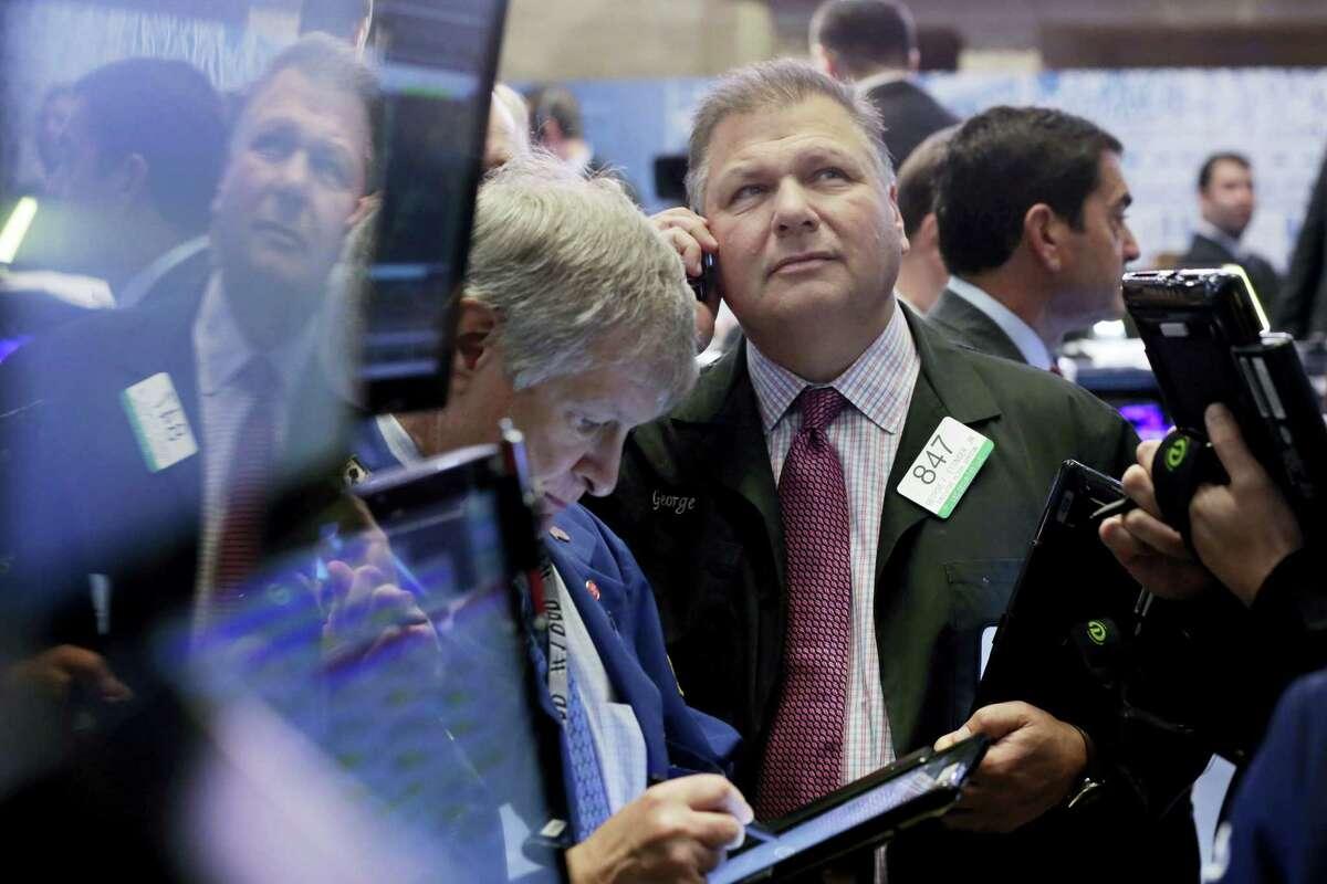 Trader George Ettinger, center, works on the floor of the New York Stock Exchange Monday.