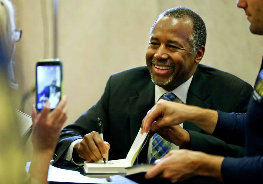 "Republican presidential candidate Ben Carson signs a copy of his book ""A More Perfect Union"" as a supporter takes his picture Oct. 23, 2015, in Topeka, Kan. Photo: The Topeka Capital-Journal Via AP   / TOPEKA CAPITAL-JOURNAL"