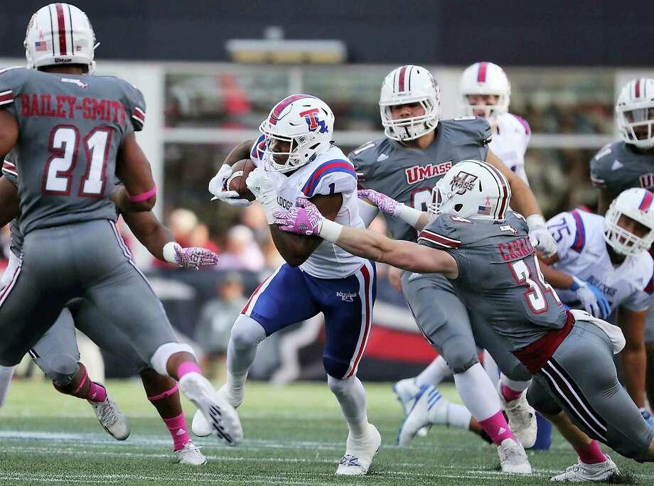 Louisiana Tech receiver Carlos Henderson breaks a tackle by UMass' Steve Casali en route to a 50-yard touchdown on Saturday. Photo: Matthew J. Lee — The Boston Globe Via AP   / Boston Globe