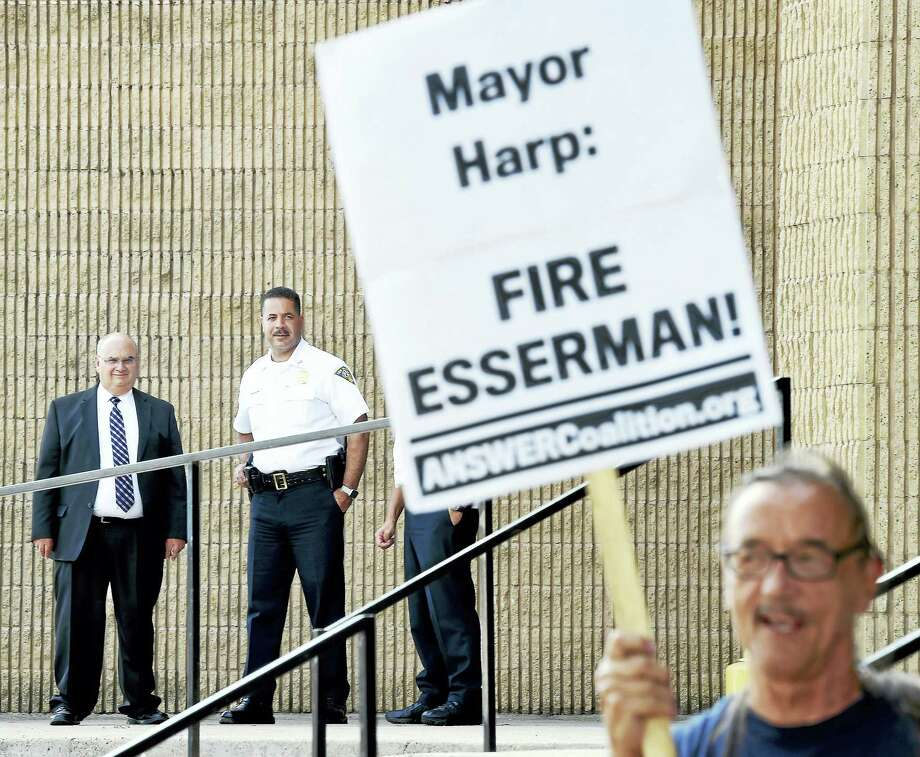"From left, Assistant Chiefs Achilles ""Archie"" Generoso and Luiz Casanova watch Norman Clement and others protest against New Haven Police Chief Dean Esserman in front of the New Haven Police Department Tuesday. Photo: Arnold Gold — New Haven Register"
