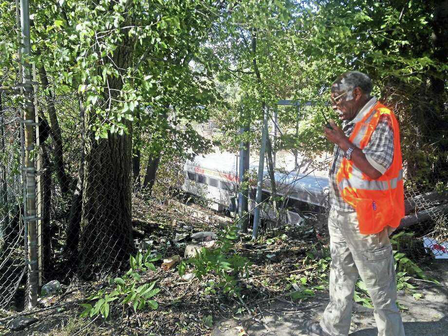An Amtrak worker radios in a request to close an opening in the fence near the railroad tracks on Wallace Street in New Haven. Photo: Juliemar Ortiz - New Haven Register