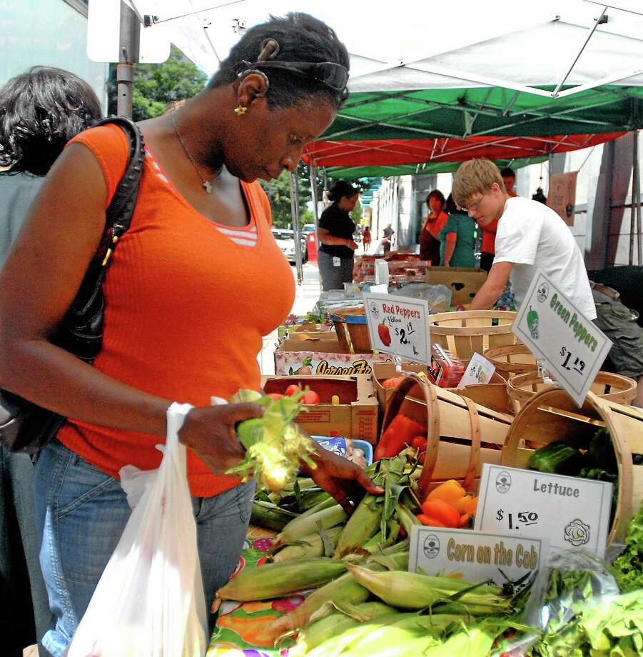 A woman shops for fresh produce during her lunch break. In rural areas, some small farmers operate on the honor system, bypassing a vendor-customer transaction. Photo: File Photo