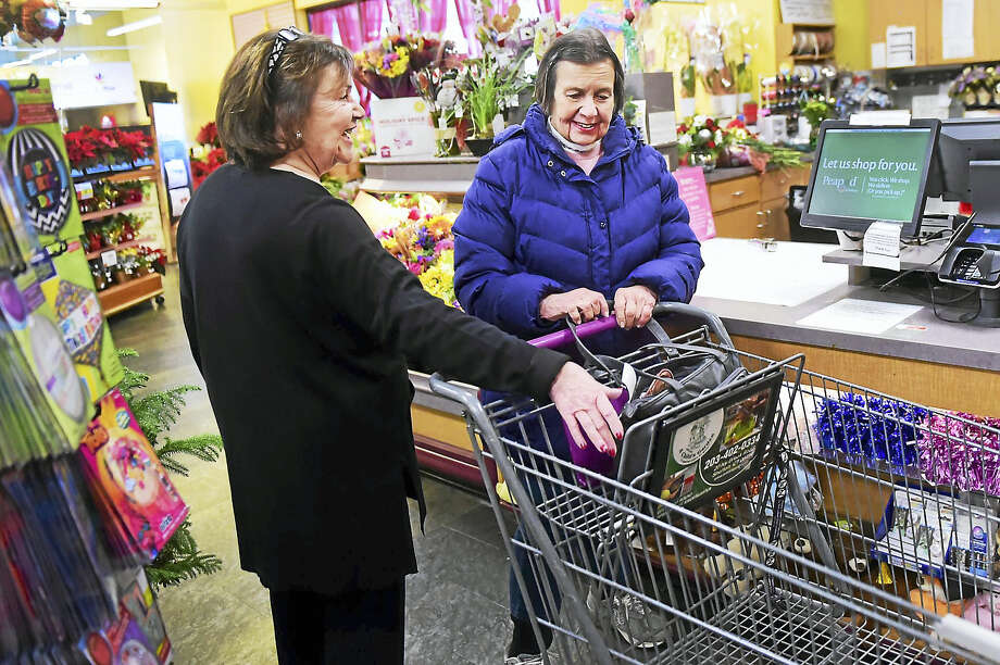 Angela DeLeon of People's United Bank, left, discusses the best ways to protect a pocketbook from would-be thieves with Stop & Shop customer Dorothy Tomasco of Derby. Photo: Peter Hvizdak — New Haven Register   / ©2016 Peter Hvizdak