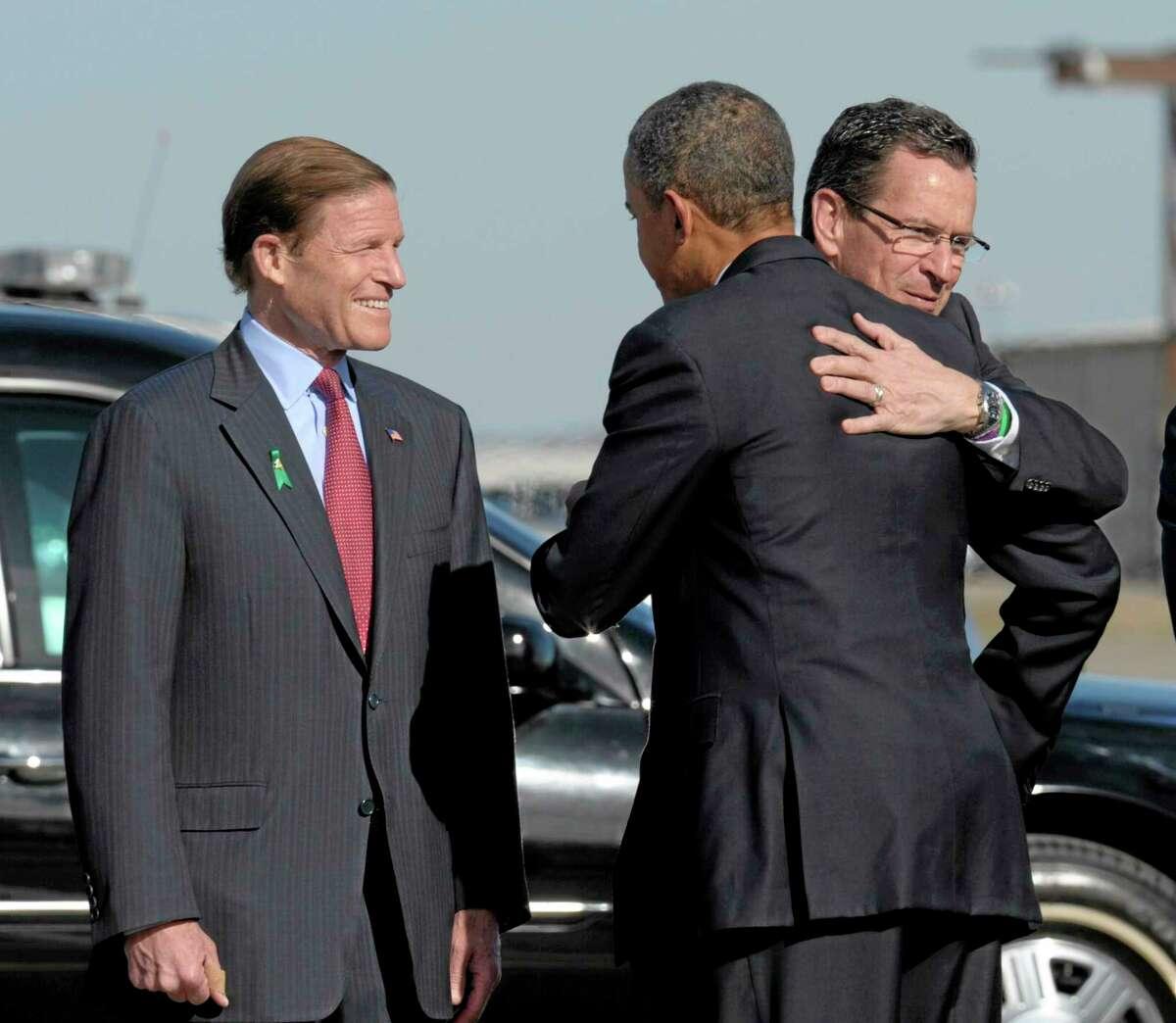 President Barack Obama hugs Connecticut Gov. Dannel P. Malloy, accompanied by Sen. Richard Blumenthal, D-Conn., left, after Obama arrived at Bradley Air Force Base, Conn. on April 8, 2013.