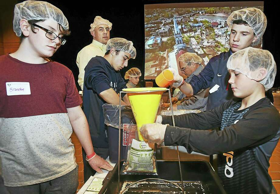 From left, Notre Dame High School freshmen Brandon Tischer, Lucas Colaci and Brendan Canning, and Gehrig Footit, 9, of Guilford volunteer Tuesday packaging meals for Haiti at the West Haven school. Photo: Catherine Avalone — New Haven Register    / New Haven RegisterThe Middletown Press