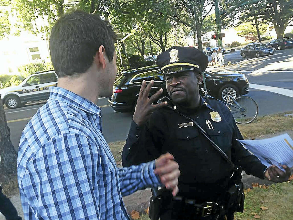 """A police officer chats with a man Friday outside St. Johns Episcopal Church for """"Koffee with a Cop."""""""