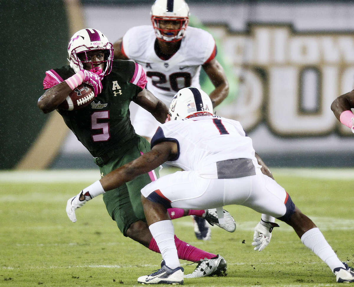 South Florida running back Marlon Mack (5) tries to avoid a tackle by UConn cornerback John Green in the first quarter on Saturday.