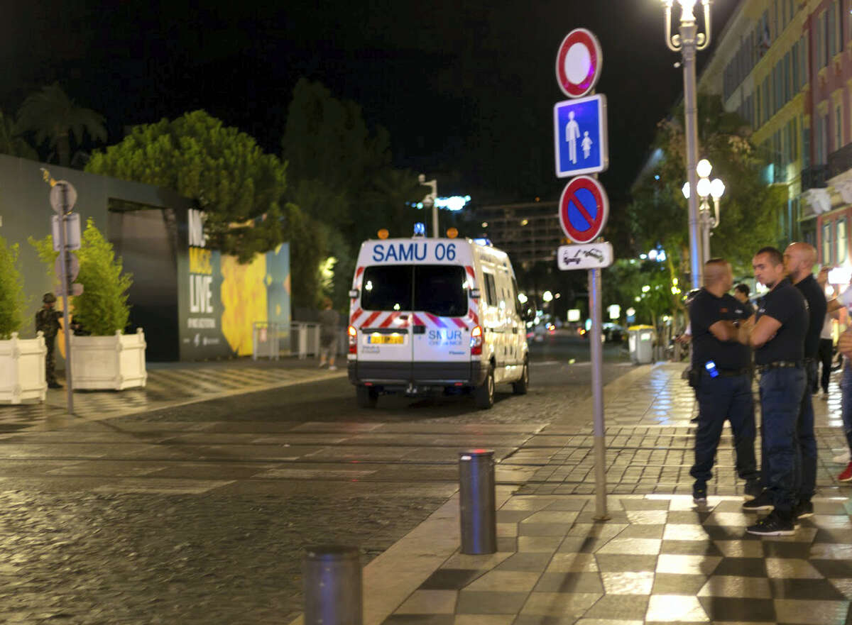 """An ambulance and police officers are seen after a truck drove on to the sidewalk and plowed through a crowd of revelers who'd gathered to watch the fireworks in the French resort city of Nice, southern France, Friday, July 15, 2016. A spokesman for France's Interior Ministry says there are likely to be """"several dozen dead"""" after a truck drove into a crowd of revelers celebrating Bastille Day in the French city of Nice."""
