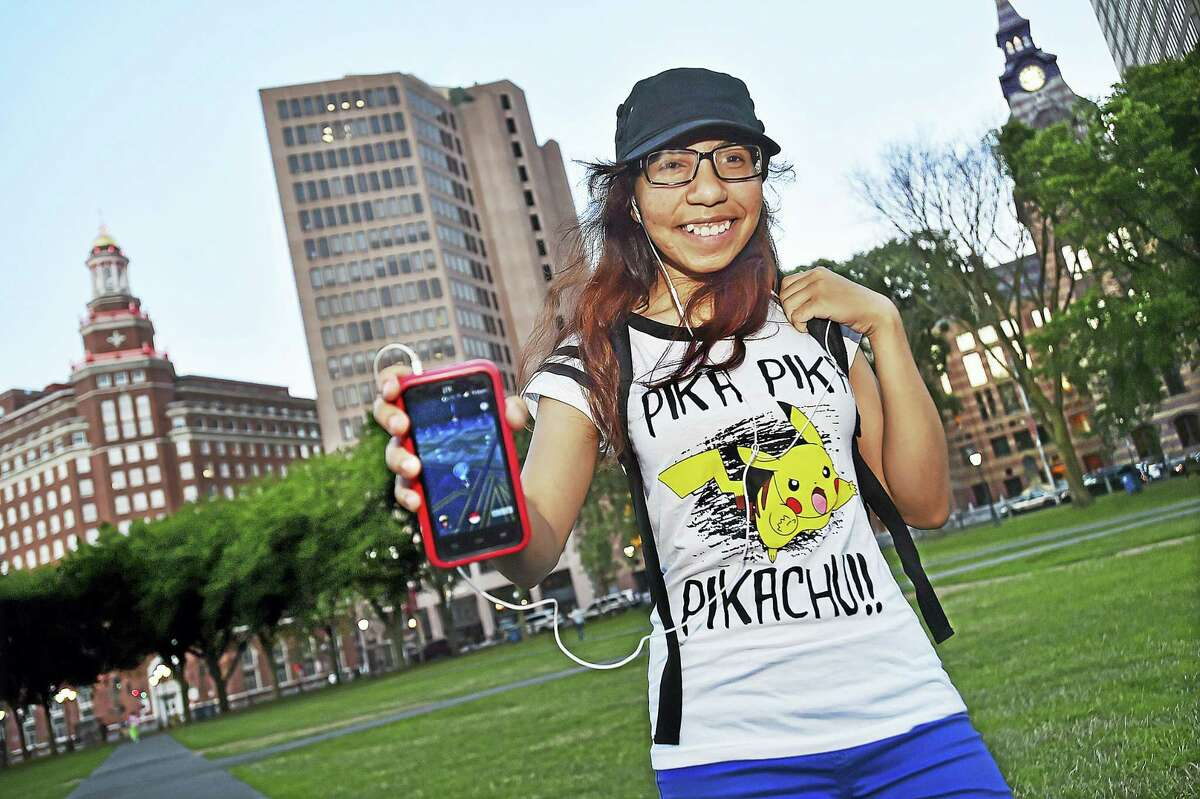 Jenny Calderon, 17, of New Haven, strolls around the New Haven Green Wednesday wearing her Pikachu shirt and blue pants, indicating she is a member of Team Mystic in search of Pokemon characters using her smartphone.