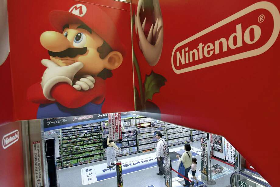 Shoppers walk under the logo of Nintendo and Super Mario characters at an electronics store in Tokyo. Photo: Shizuo Kambayashi — The Associated Press File Photo   / Copyright 2016 The Associated Press. All rights reserved. This material may not be published, broadcast, rewritten or redistribu