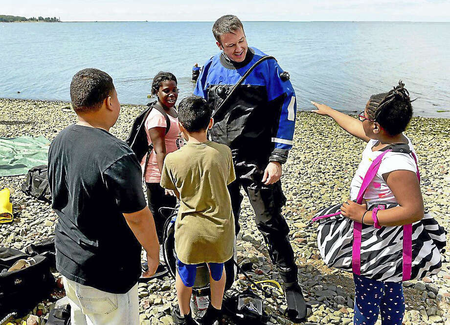 New Haven Police Underwater Search and Recovery Team member Officer Christian Brukart engages with children from the New Haven Police Athletic League summer camp at Fort Nathan Hale at Black Rock in New Haven. Photo: (Peter Hvizdak - New Haven Register)    / ?2016 Peter Hvizdak