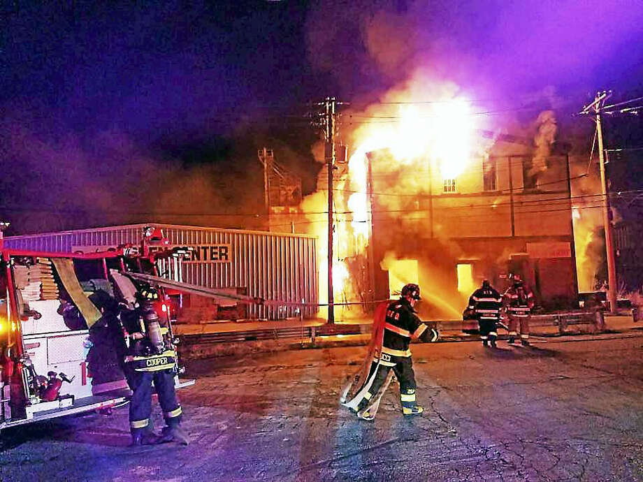 Authorities are investigating after a three-alarm fire scorched a building at the corner of Main and Caroline streets early Sunday morning. Photo: Photo By Derby Fire Chief Chief Kurt Kemmesies