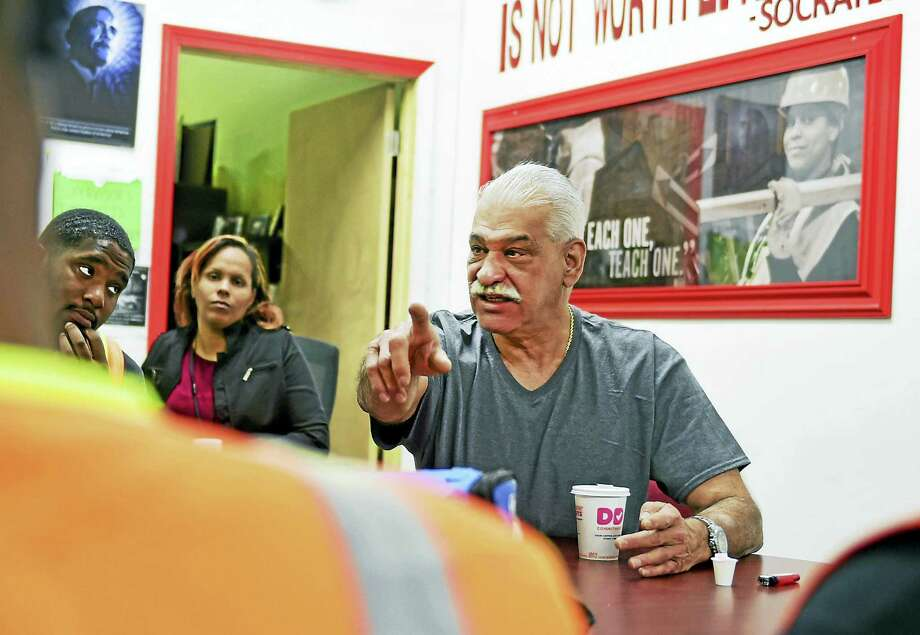 EMERGE Connecticut Executive Director Dan Jusino shares an early-morning conversation on personal responsibility with EMERGE crew members who were recently released from prison and  are on a salary through EMERGE in a work-reentry program in New Haven on Sept. 2916. In the background is Johanna Cartagena, EMERGE assistant crew chief. Photo: Peter Hvizdak — New Haven Register   / ©2016 Peter Hvizdak