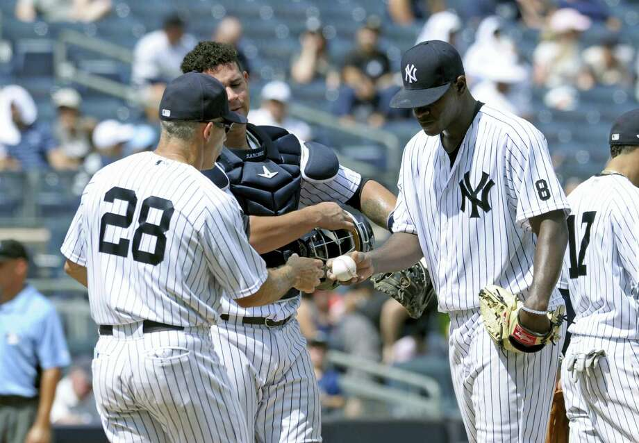Yankees pitcher Luis Severino, right, hands the ball to manager Joe Girardi in the fourth inning on Sunday. Photo: Bill Kostroun — The Associated Press   / FR51951 AP