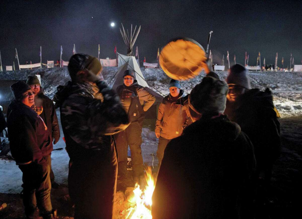 Campers gather around a fire to sing and drum traditional Native American social songs at the Oceti Sakowin camp where people have gathered to protest the Dakota Access oil pipeline in Cannon Ball, N.D. on Sunday, Dec. 4, 2016. U.S. Army Corps of Engineers spokeswoman Moria Kelley said in a news release Sunday that the administration will not allow the four-state, $3.8 billion pipeline to be built under Lake Oahe, a Missouri River reservoir where construction had been on hold.