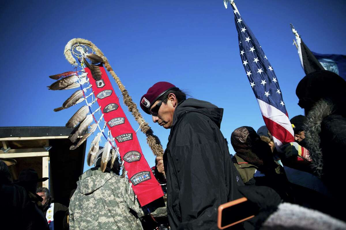 Native American veterans join an interfaith ceremony at the Oceti Sakowin camp where people have gathered to protest the Dakota Access oil pipeline in Cannon Ball, N.D. on Sunday, Dec. 4, 2016. Tribal elders have asked the military veterans joining the large Dakota Access pipeline protest encampment not to have confrontations with law enforcement officials, an organizer with Veterans Stand for Standing Rock said Sunday, adding the group is there to help out those who've dug in against the four-state, $3.8 billion project.
