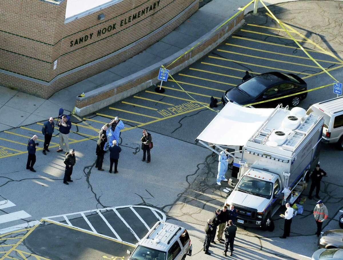 This Dec. 14, 2012, aerial file photo shows officials standing outside of Sandy Hook Elementary School in Newtown.