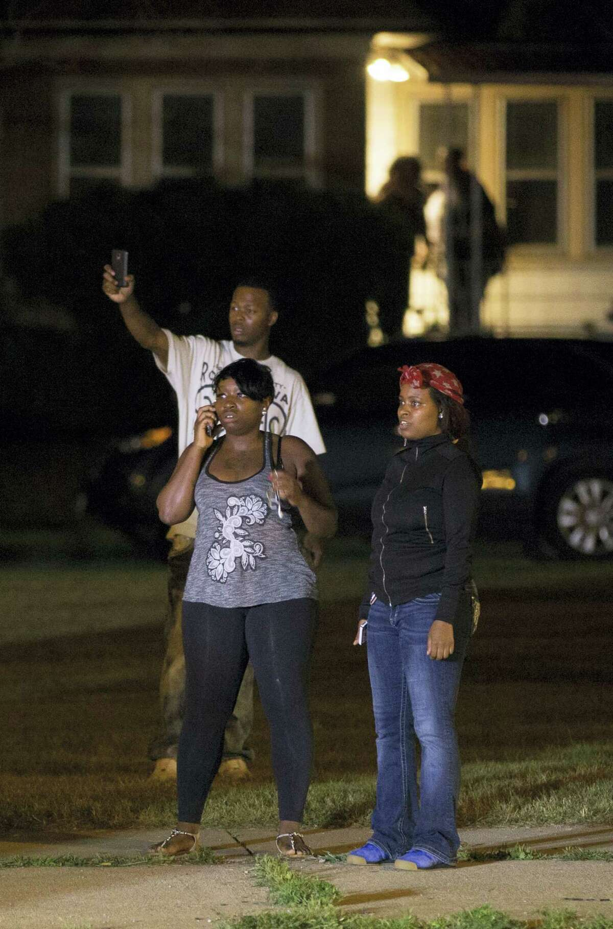 Bystanders watch as a crowd of more than 100 people gathers following the fatal shooting of a man in Milwaukee on Aug. 13, 2016. The gathering occurred in the neighborhood where a Milwaukee officer shot and killed a man police say was armed hours earlier during a foot chase.