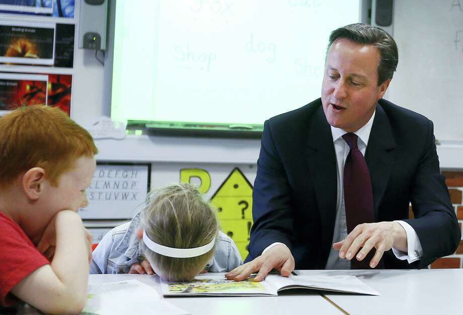 """In this Wednesday, April 8, 2015, file photo Britain's Prime Minister David Cameron reads a book to Lucy Howarth, 6, and Will Spibey, 5, left, during a visit to Sacred Heart RC primary school in Westhoughton near Bolton, England. When Cameron was elected leader of Britain's Conservative Party, the press called him the """"heir to Blair."""" Like Labour premier Tony Blair, he was a young leader who dragged his sometimes reluctant party toward the political center. Cameron steps down Wednesday, July 13, 2016, after six years as prime minister. Photo: AP Photo/Kirsty Wigglesworth, Pool, File    / AP POOL"""