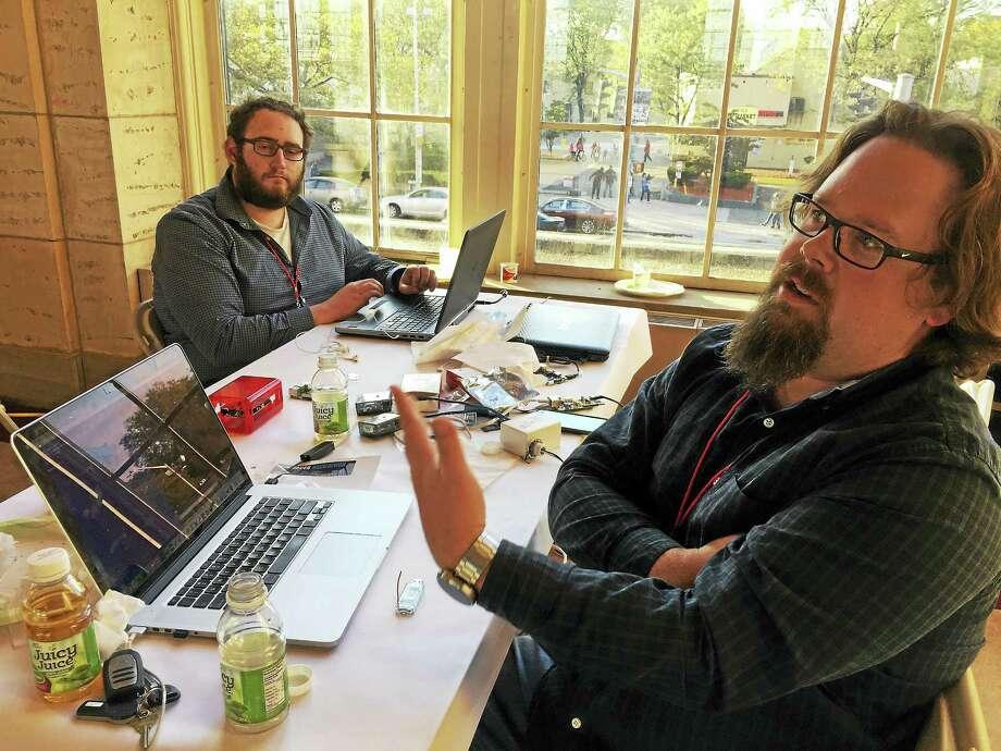 Engineer Ryan Zaveruha talks about hacking during the New Haven Hackathon on Saturday, Oct. 15, at Union Station. Zaveruha's team member, Matt Curreri sits in the back. Photo: Esteban L. Hernandez — New Haven Register