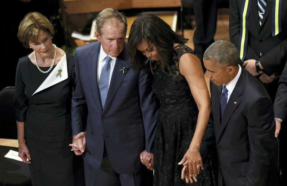 Former first lady Laura Bush, left, former President George W. Bush, first lady Michelle Obama, and President Barack Obama attend an interfaith memorial service for the fallen police officers and members of the Dallas community at the Morton H. Meyerson Symphony Center in Dallas on Tuesday. Photo: ASSOCIATED PRESS   / Copyright 2016 The Associated Press. All rights reserved. This material may not be published, broadcast, rewritten or redistribu