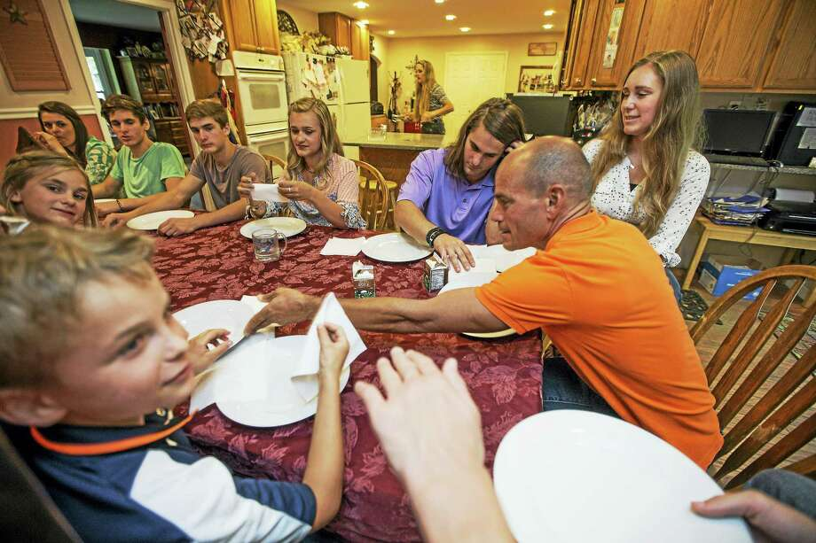 Dinnertime can be hectic for the Fatzinger family, although they've learned shortcuts to speed up the process through sharing, passing silverware, and having great manners. Photo by April Greer for The Washington Post Photo: For The Washington Post / For The Washington Post