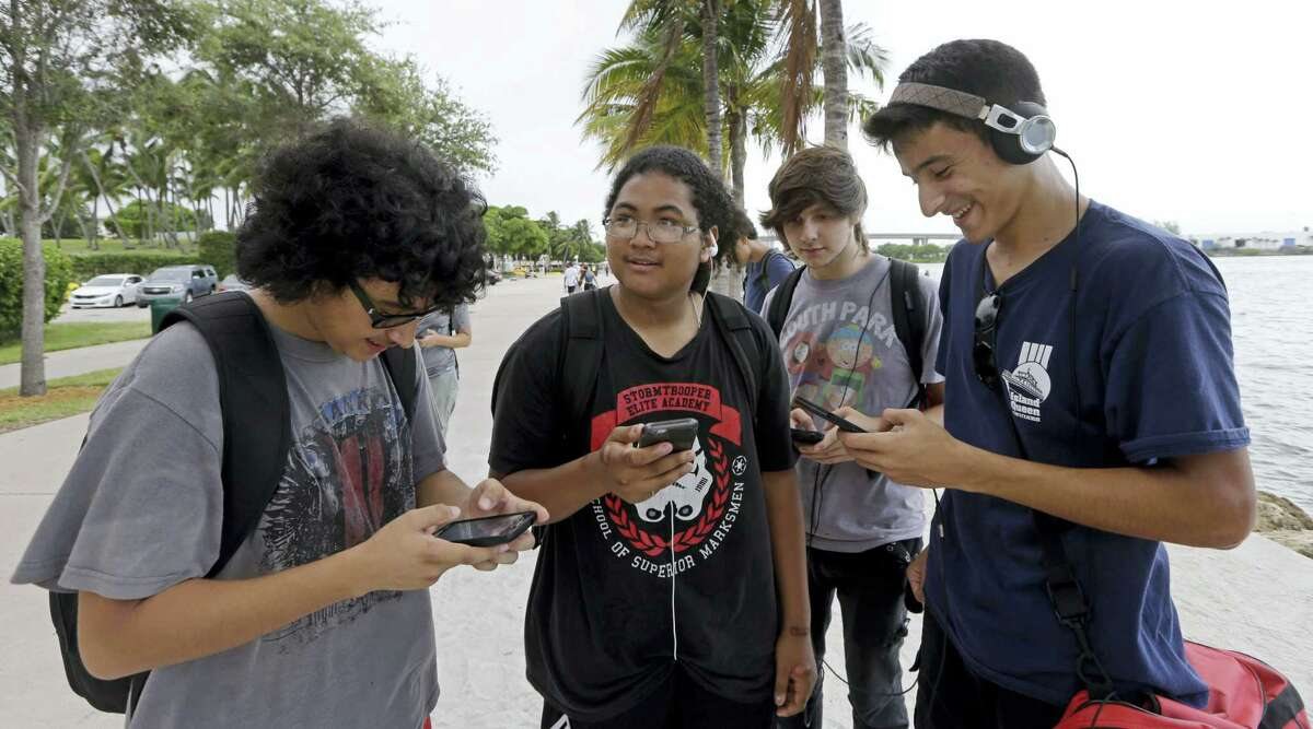 """Pokemon Go players Brian Vega, left, Peyton Ruiz, second from left, and Max Marrero, right, check their smartphones as they try to find Pokemon, Tuesday, July 12, 2016, at Bayfront Park in downtown Miami. The """"Pokemon Go"""" craze has sent legions of players hiking around cities and battling with """"pocket monsters"""" on their smartphones. It marks a turning point for augmented reality, or technology that superimposes a digital facade on the real world."""