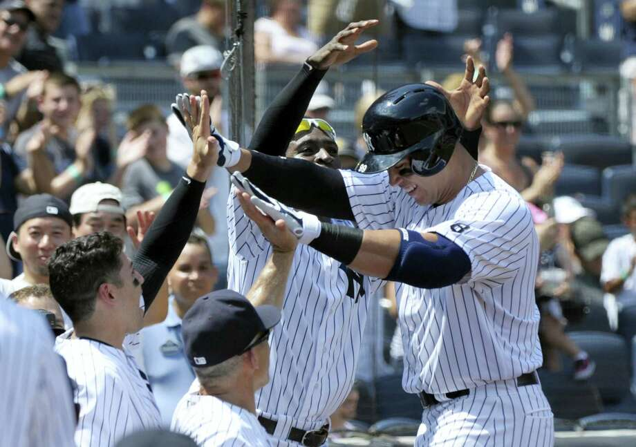 Aaron Judge, right, celebrates with teammates after hitting a home run during the second inning on Saturday. Photo: Bill Kostroun — The Associated Press   / FR51951 AP