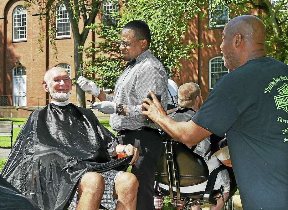 Master barber Omar Sanchez, of Sangster Barber & Salon in Hamden, gives a free haircut to Joe Murphy on the New Haven Green Wednesday, as event organizer Jesse Hardy shows Murphy a picture on his smartphone. Photo: Catherine Avalone — New Haven Register   / New Haven RegisterThe Middletown Press