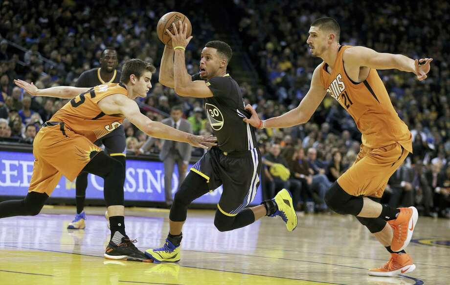 Golden State Warriors' Stephen Curry, center, drives between Phoenix Suns' Dragan Bender, left, and Alex Len during the second half of an NBA basketball game Saturday, Dec. 3, 2016 in Oakland, Calif. Photo: AP Photo/Ben Margot   / Copyright 2016 The Associated Press. All rights reserved.
