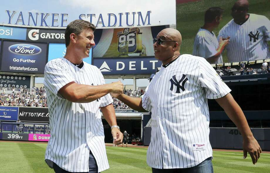 Former Yankees' Tino Martinez, left, and Bernie Williams embrace as the 1996 team was honored before Saturday's game against the Rays at Yankee Stadium. Photo: John Munson — The Star-Ledger Via AP   / Pool The Star-Ledger