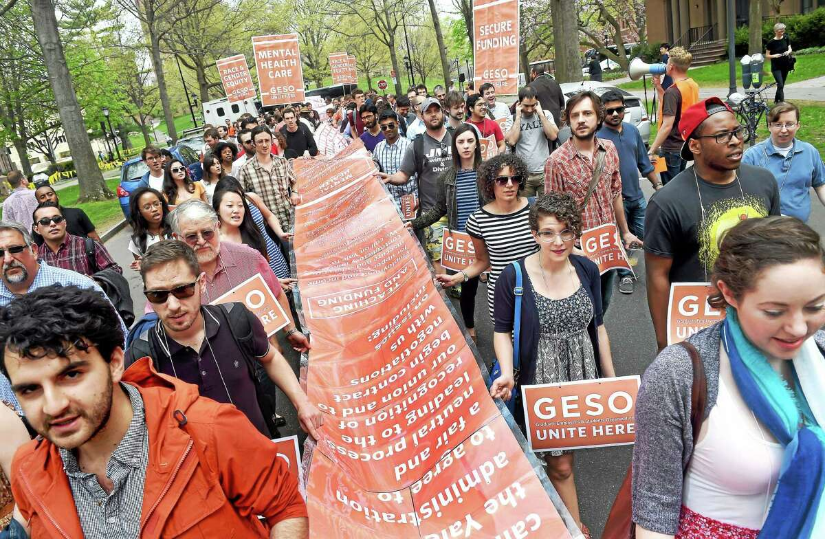 Arnold Gold — New Haven Register/File GESO members and supporters carry a petition calling on Yale University to negotiate on issues of secure pay, mental health services and racial and gender equity as they march down march down Hillhouse Ave. in New Haven on 5/5/2015.