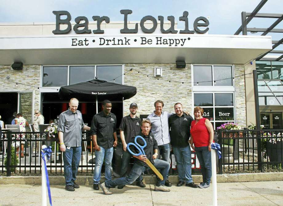 "NEWEST LOCATION: A ribbon-cutting was held recently to celebrate the opening of Bar Louie's newest location in Milford, in front of the Connecticut Post Mall. The casual restaurant specializes in oversized sandwiches, signature cocktails and a large assortment of beers, microbrews and wines. Here, the Bar Louie Milford team poses with the ""big scissors"" after Mayor Benjamin Blake cut the ribbon. Photo: CONTRIBUTED PHOTO — NELL MOLL"