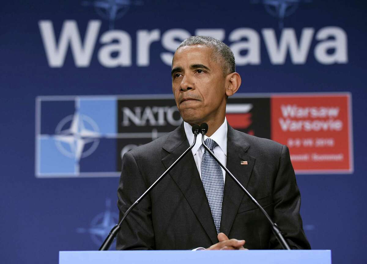 President Barack Obama pauses while speaking about the events in Dallas at the beginning of his news conference at PGE National Stadium in Warsaw, Poland, Saturday, July 9, 2016. Obama is in Warsaw attending the NATO Summit.
