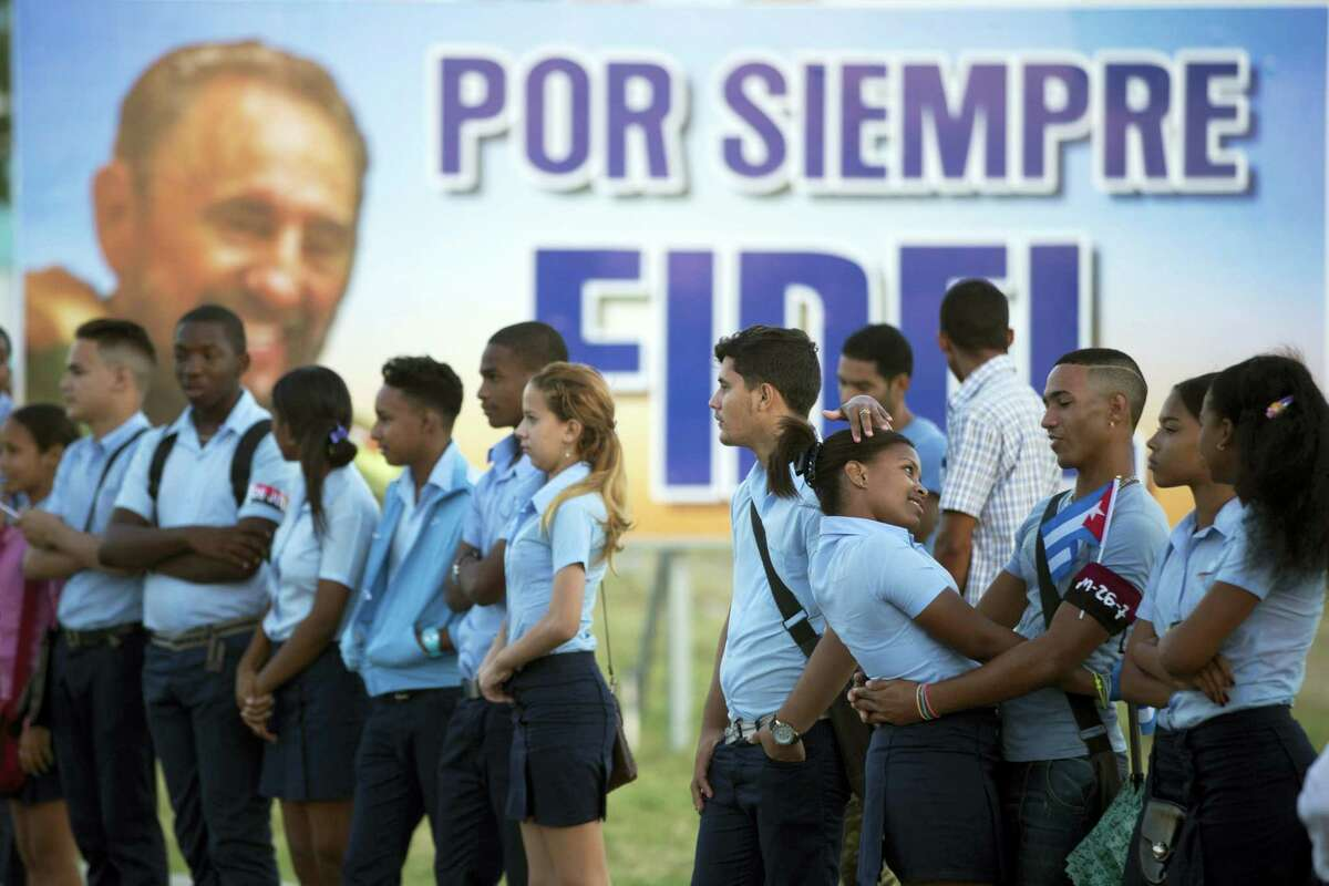 Students wait to see the ashes of Cuba's leader Fidel Castro driven to the Santa Ifigenia cemetery in Santiago, Cuba, Sunday, Dec. 4, 2016. The motorcade carrying the ashes made i's final journey towards the cemetery as thousands of people lined the short route from the Plaza Antonio Maceo.(AP Photo/Ricardo Mazalan)